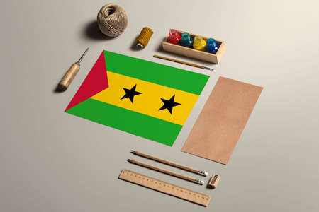 Sao Tome And Principe calligraphy concept, accessories and tools for beautiful handwriting, pencils, pens, ink, brush, craft paper and cardboard crafting on wooden table.