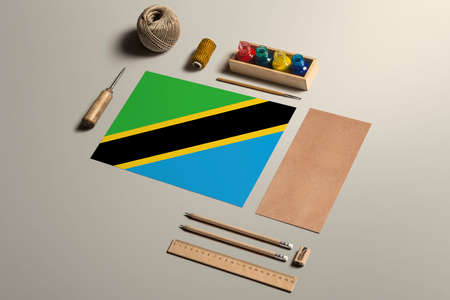 Tanzania calligraphy concept, accessories and tools for beautiful handwriting, pencils, pens, ink, brush, craft paper and cardboard crafting on wooden table.