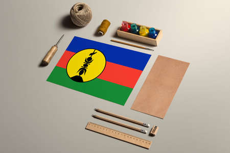 New Caledonia calligraphy concept, accessories and tools for beautiful handwriting, pencils, pens, ink, brush, craft paper and cardboard crafting on wooden table.