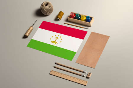 Tajikistan calligraphy concept, accessories and tools for beautiful handwriting, pencils, pens, ink, brush, craft paper and cardboard crafting on wooden table.