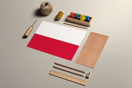 Poland calligraphy concept, accessories and tools for beautiful handwriting, pencils, pens, ink, brush, craft paper and cardboard crafting on wooden table.