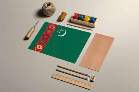 Turkmenistan calligraphy concept, accessories and tools for beautiful handwriting, pencils, pens, ink, brush, craft paper and cardboard crafting on wooden table.