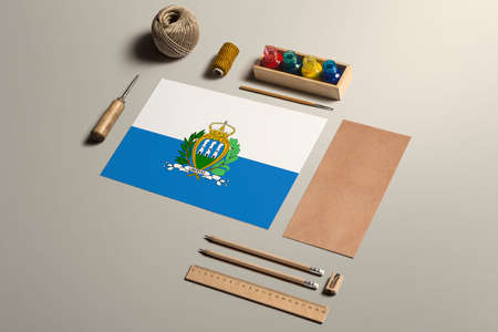 San Marino calligraphy concept, accessories and tools for beautiful handwriting, pencils, pens, ink, brush, craft paper and cardboard crafting on wooden table.