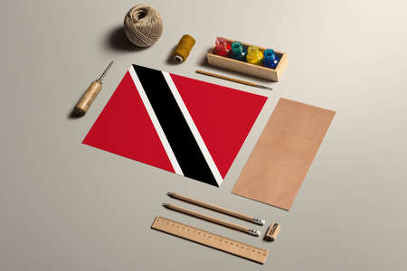 Trinidad And Tobago calligraphy concept, accessories and tools for beautiful handwriting, pencils, pens, ink, brush, craft paper and cardboard crafting on wooden table.