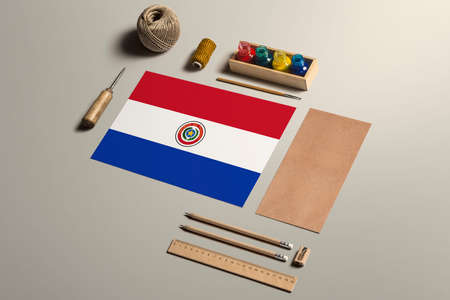 Paraguay calligraphy concept, accessories and tools for beautiful handwriting, pencils, pens, ink, brush, craft paper and cardboard crafting on wooden table.