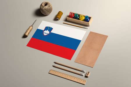 Slovenia calligraphy concept, accessories and tools for beautiful handwriting, pencils, pens, ink, brush, craft paper and cardboard crafting on wooden table.
