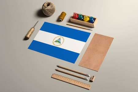 Nicaragua calligraphy concept, accessories and tools for beautiful handwriting, pencils, pens, ink, brush, craft paper and cardboard crafting on wooden table.
