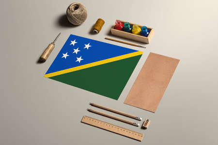 Solomon Islands calligraphy concept, accessories and tools for beautiful handwriting, pencils, pens, ink, brush, craft paper and cardboard crafting on wooden table.