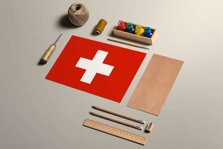 Switzerland calligraphy concept, accessories and tools for beautiful handwriting, pencils, pens, ink, brush, craft paper and cardboard crafting on wooden table.