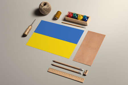 Ukraine calligraphy concept, accessories and tools for beautiful handwriting, pencils, pens, ink, brush, craft paper and cardboard crafting on wooden table.