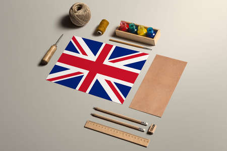 United Kingdom calligraphy concept, accessories and tools for beautiful handwriting, pencils, pens, ink, brush, craft paper and cardboard crafting on wooden table.