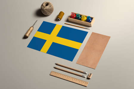 Sweden calligraphy concept, accessories and tools for beautiful handwriting, pencils, pens, ink, brush, craft paper and cardboard crafting on wooden table.