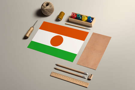 Niger calligraphy concept, accessories and tools for beautiful handwriting, pencils, pens, ink, brush, craft paper and cardboard crafting on wooden table.