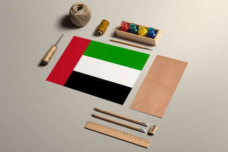 United Arab Emirates calligraphy concept, accessories and tools for beautiful handwriting, pencils, pens, ink, brush, craft paper and cardboard crafting on wooden table.