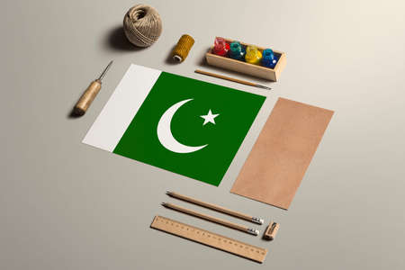 Pakistan calligraphy concept, accessories and tools for beautiful handwriting, pencils, pens, ink, brush, craft paper and cardboard crafting on wooden table. 免版税图像