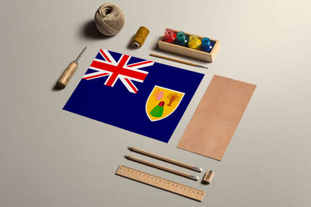 Turks And Caicos Islands calligraphy concept, accessories and tools for beautiful handwriting, pencils, pens, ink, brush, craft paper and cardboard crafting on wooden table.