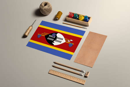 Swaziland calligraphy concept, accessories and tools for beautiful handwriting, pencils, pens, ink, brush, craft paper and cardboard crafting on wooden table.