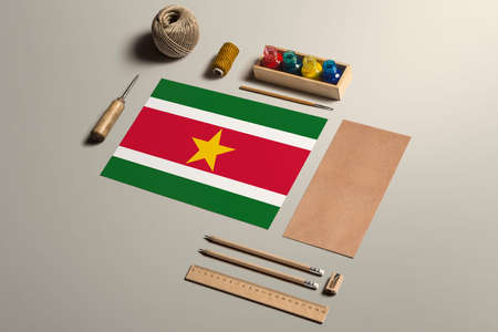 Suriname calligraphy concept, accessories and tools for beautiful handwriting, pencils, pens, ink, brush, craft paper and cardboard crafting on wooden table.