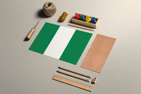 Nigeria calligraphy concept, accessories and tools for beautiful handwriting, pencils, pens, ink, brush, craft paper and cardboard crafting on wooden table.