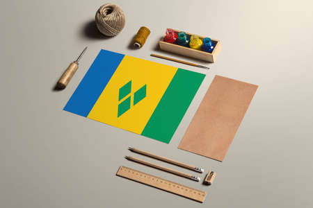 Saint Vincent And The Grenadines calligraphy concept, accessories and tools for beautiful handwriting, pencils, pens, ink, brush, craft paper and cardboard crafting on wooden table.