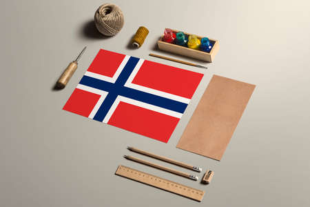Norway calligraphy concept, accessories and tools for beautiful handwriting, pencils, pens, ink, brush, craft paper and cardboard crafting on wooden table.