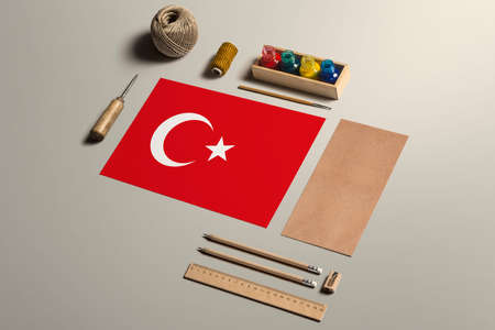 Turkey calligraphy concept, accessories and tools for beautiful handwriting, pencils, pens, ink, brush, craft paper and cardboard crafting on wooden table.