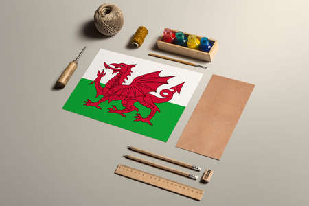 Wales calligraphy concept, accessories and tools for beautiful handwriting, pencils, pens, ink, brush, craft paper and cardboard crafting on wooden table.