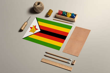 Zimbabwe calligraphy concept, accessories and tools for beautiful handwriting, pencils, pens, ink, brush, craft paper and cardboard crafting on wooden table.