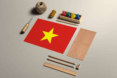Vietnam calligraphy concept, accessories and tools for beautiful handwriting, pencils, pens, ink, brush, craft paper and cardboard crafting on wooden table.