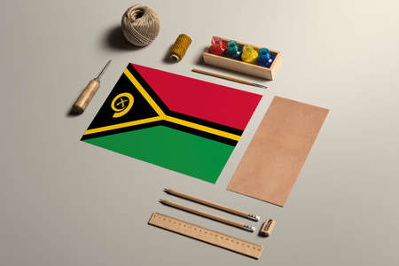 Vanuatu calligraphy concept, accessories and tools for beautiful handwriting, pencils, pens, ink, brush, craft paper and cardboard crafting on wooden table.