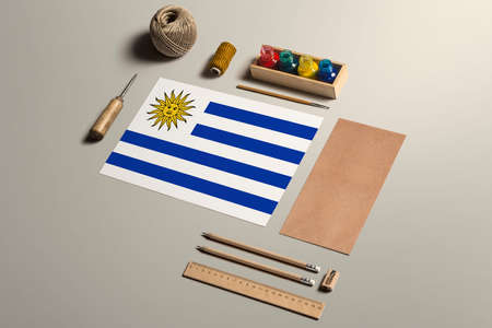 Uruguay calligraphy concept, accessories and tools for beautiful handwriting, pencils, pens, ink, brush, craft paper and cardboard crafting on wooden table.