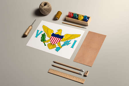 United States Virgin Islands calligraphy concept, accessories and tools for beautiful handwriting, pencils, pens, ink, brush, craft paper and cardboard crafting on wooden table.