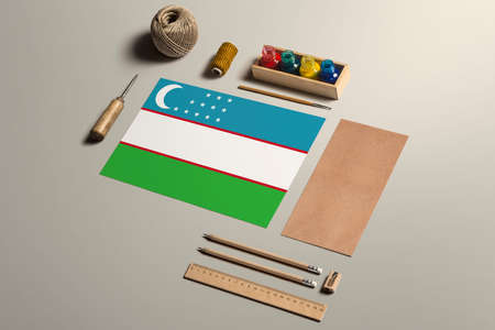Uzbekistan calligraphy concept, accessories and tools for beautiful handwriting, pencils, pens, ink, brush, craft paper and cardboard crafting on wooden table. 免版税图像