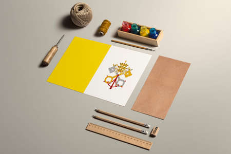 Vatican City calligraphy concept, accessories and tools for beautiful handwriting, pencils, pens, ink, brush, craft paper and cardboard crafting on wooden table.