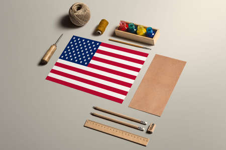 United States calligraphy concept, accessories and tools for beautiful handwriting, pencils, pens, ink, brush, craft paper and cardboard crafting on wooden table.