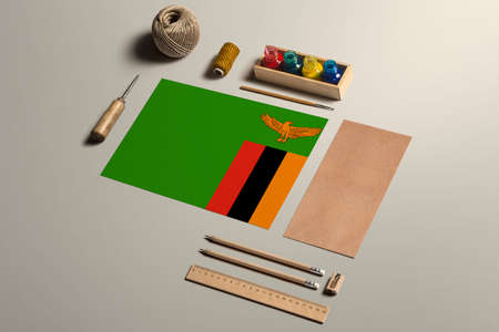 Zambia calligraphy concept, accessories and tools for beautiful handwriting, pencils, pens, ink, brush, craft paper and cardboard crafting on wooden table.