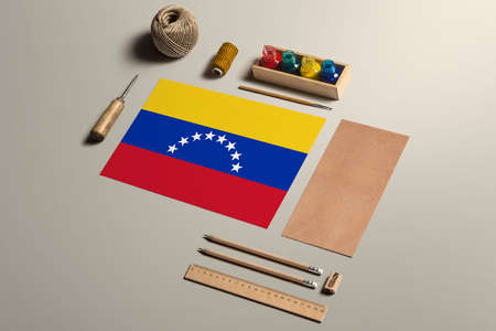 Venezuela calligraphy concept, accessories and tools for beautiful handwriting, pencils, pens, ink, brush, craft paper and cardboard crafting on wooden table.
