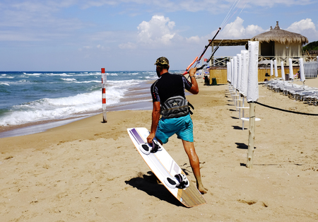 Man surfer in wetsuits with kite equipment for surfing, in Sabaudia, Lazio, Italy