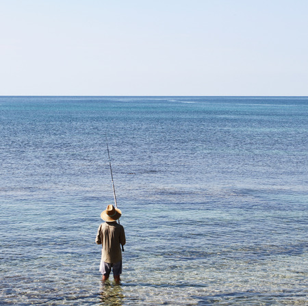 Fisherman with wide oriental style hat and fishing rod. seen from behind. Salento, Apulia, Italy Stock Photo