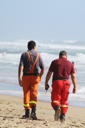 Two rescuers walking on the beach with the transceiver in the hand. In the background some swimmers take a bath despite the rough sea.