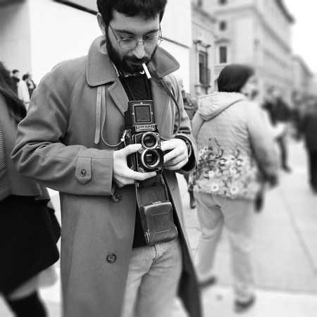 Bologna, Italy ? ?? November 05, 2018: Close-up of Hipster man with the vintage Rolleiflex camera. Photographer with a famous retro camera. Bologna, Italy