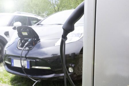 EV Car or Electric car at charging station with the power cable supply plugged in on blurred nature with sun light background. Eco-friendly alternative energy concept