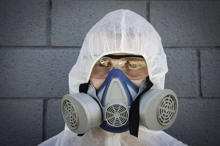 Man in protective clothing and a gas mask on an urban gray background - Worker ready for disinfection and decontamination for people healthcare during coronavirus lockdown - Focus on eyes