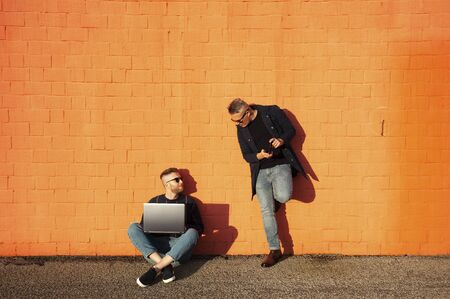Two friends in casual-wear in urban contest with digital devices. Young caucasian man sitting cross-legged on ground and working on laptop. The other man standing with smartphone. Red wall on the background.