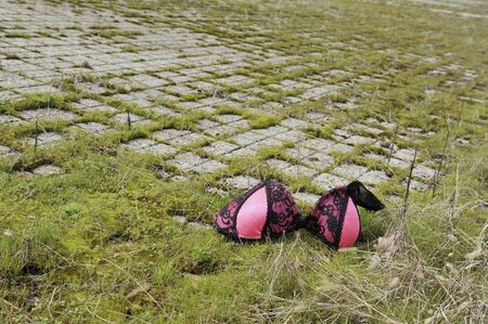 Mysterious abandoned parking with bra on flooring. Discarded women's underwear thrown on the pavement. Concept of the social issues, incident, loss, disappearance of a person or the crime and suicide.