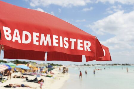 Red lifeguard umbrella on a beach against blue sky. Some bathers ont he background. The text on the umbrella Bademeister translates as Lifeguard, for german bathers. Risk and rescue concept. Tyrrhenian sea, South Italy.