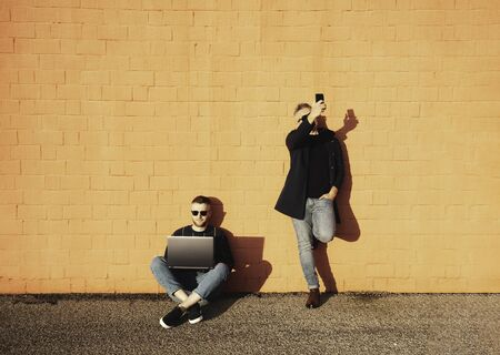 Two friends or colleagues with digital devices during lunch break - Young caucasian man sitting cross-legged on ground and working on laptop - The other man standing and taking selfie with smartphone