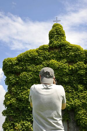 Back view of a tourist photographing an old ivy-covered church in countryside in a summer day - Concept of nature recovering its spaces - Main focus on the man - Eco-sustainable tourism and wanderlust