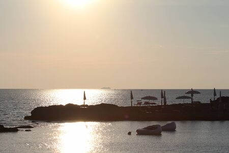 Sunset in the beautiful bay with rock beach and floating pink beds -