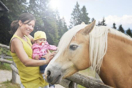 Mom with her daughter are meeting a horse in the educational farm. Happy childhood concept. Pet therapy concept in countryside.